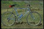 Breezer  number 1 standing in field, Crested Butte, CO, September 1979. Built by Joe Breeze in Mill Valley, CA, September 1977. Owned by Joe Breeze. Light blue frame. Static side view. At least 5 different bikes were shot at this site with the same background: Breezer, Richman, Pro Cruiser, Cook Bros., and a Ritchey.