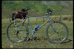 Jeffrey Richman bike standing in field, Crested Butte, CO, September 1979. Built in Santa Rosa, CA, late to 1978 or sometime 1979 September or before. Owned by Michael Castelli of Point Reyes, CA. Light blue frame. Static side view.