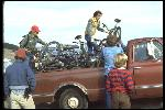 At the Azalea Hill drop off point for Repack. Bikes are unloaded from Vince Carlton's brown Chevrolet pick-up truck. Left to right: Mark Green, standing, Charlie Kelly unloading his Excelsior, Alan Bonds helping Joe Breeze with Breezer #1, unidentified. Side view of truck with lots of bikes. October, 1977.